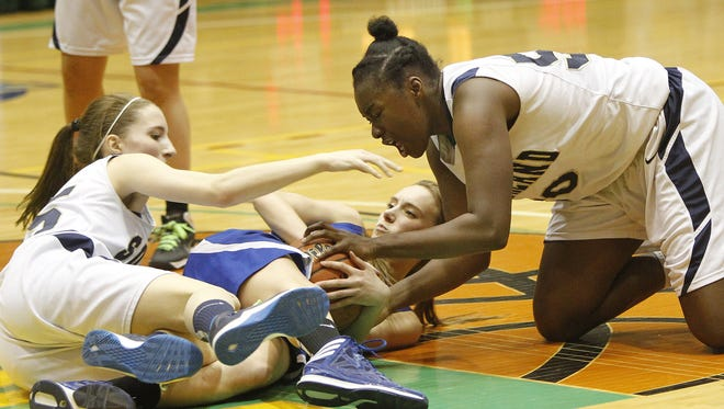 Sutherland's Santita Ebangwese, right, and Ally Judd wrestle for a ball during the state Class A girls basketball semifinals at Hudson Valley Community College last season.