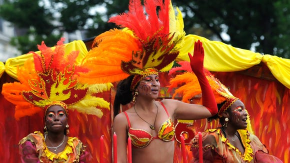 Brightly colored costumes and parade floats take part in Summer Carnival in Rotterdam.