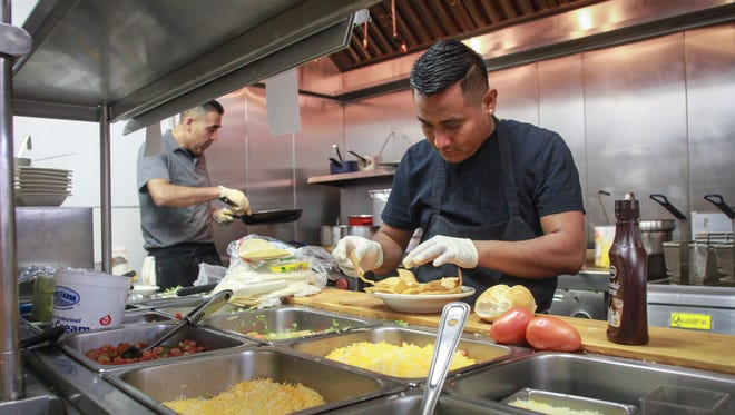 Owner Abel Guerrero, left, works in the kitchen of Mexico Lindo with head chef Jesus Perez.business. The popular Brick restaurant recently reopened more than a year after losing its lease in another building across town.