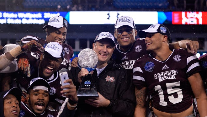 CHARLOTTE, NC - DECEMBER 30:  Head coach Dan Mullen and the Mississippi State Bulldogs celebrate with the trophy after a win over the North Carolina State Wolfpack during the Belk Bowl at Bank of America Stadium on December 30, 2015 in Charlotte, North Carolina. Mississippi State won 51-28.  (Photo by Grant Halverson/Getty Images)