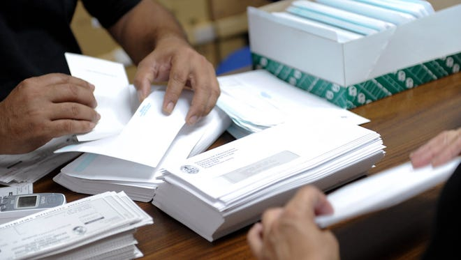 In this file photo, Department of Administration employees stuff envelopes with tax refund checks.