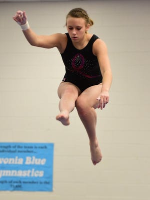 Livonia Red's Jackie Dziurgot  elevates on the balance beam during a meet earlier this season.