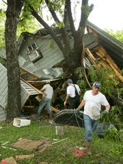Jeremy Steele, left, Ric Jaime, center, and Keith McNabb salvage belongings at their friend Mike Cook's house near Wimberley, Texas, on Sunday, May 24, 2015. Up to 400  homes in the town of Wimberley were washed away by flash floods along the Blanco River, which rose 26 feet in just one hour and left piles of wreckage 20 feet high, Texas authorities said.