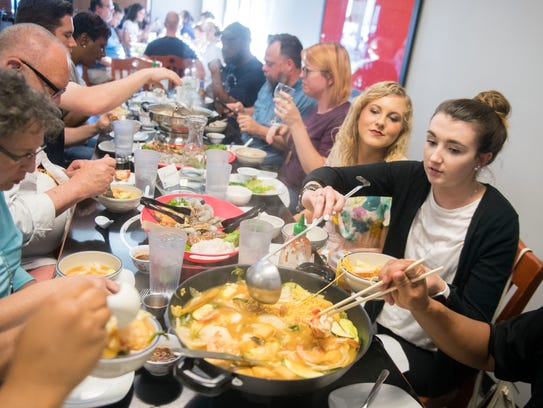 Diners participate in a hot pot dinner at Sticky Rice