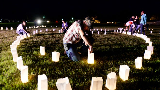 Chris Dodge lights a candle luminary for Jeremy Mardis.