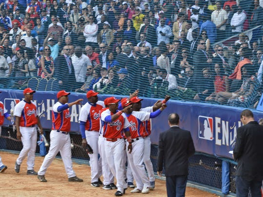 Members of the Cuban national team wave to Cuban President