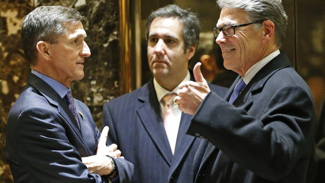 Retired U.S. Army Lt. Gen. Michael T. Flynn (left) chats with former Texas Gov. Rick Perry (right) and Trump attorney Michael D. Cohen (center) in the lobby at Trump Tower on Monday.