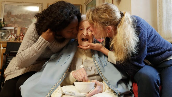 Emma Morano, 117 years hold, is kissed by her caretakers Malgorzat Ceglinska, right, and Yamilec Vergara, in the day of her birthday in Verbania, Italy, Tuesday, Nov. 29, 2016.  At 117 years of age, Emma is now the oldest person in the world and is believed to be the last surviving person in the world who was born in the 1800s, coming into the world on Nov. 29, 1899.