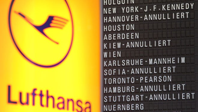 In this file photo from Nov. 23, 2016, a flight-display board showing canceled flights is seen next to a Lufthansa logo at the Frankfurt Airport.