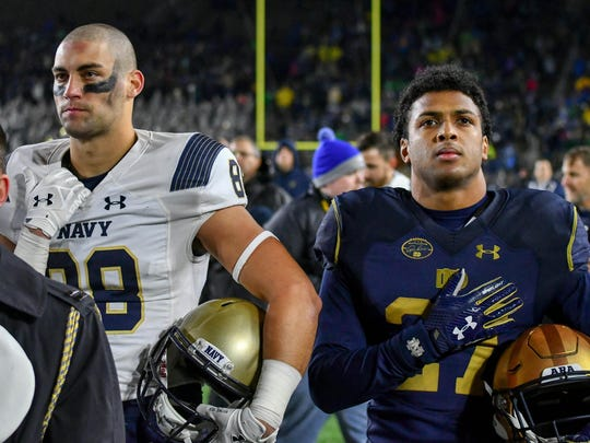 Navy Midshipmen wide receiver Tyler Carmona (88) and Notre Dame Fighting Irish cornerback Julian Love (27) stand for the United States Naval Academy Alma Mater after the game at Notre Dame Stadium.