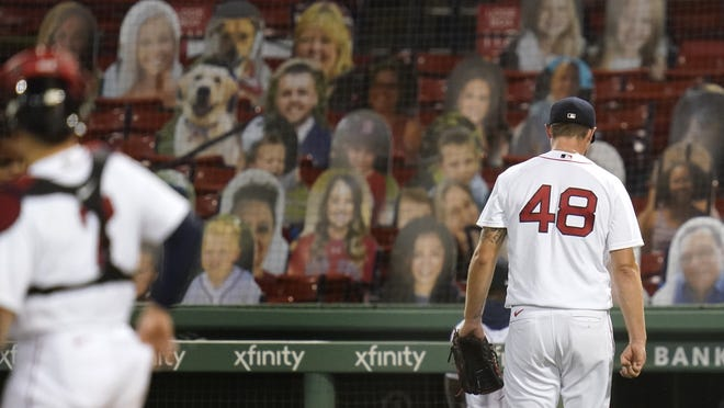 Red Sox pitcher Colten Brewer (right) heads to the clubhouse after being pulled from after loading the bases against the Braves during the fifth inning of a baseball game, Monday, Aug. 31, 2020, in Boston.