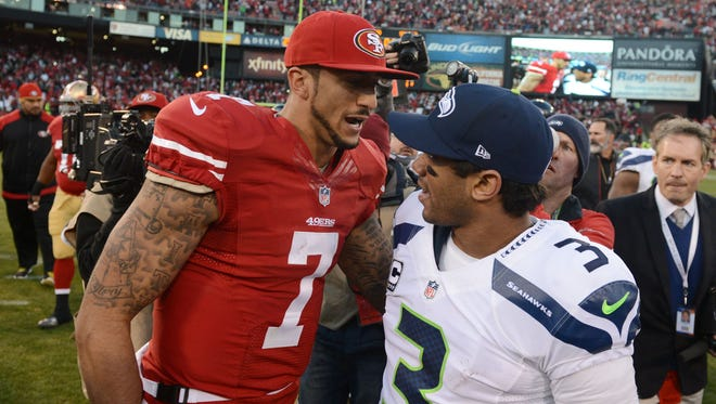 San Francisco 49ers quarterback Colin Kaepernick (7) shakes hands with Seattle Seahawks quarterback Russell Wilson (3) after the game at Candlestick Park.