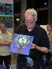 """Jim Stingl holds his finished painting, """"You make my heart sing,"""" after an evening at Arte Wine and Painting Studio, 1442 Underwood Ave., Wauwatosa. The finished painting was part of a Milwaukee Art Museum benefit last weekend."""