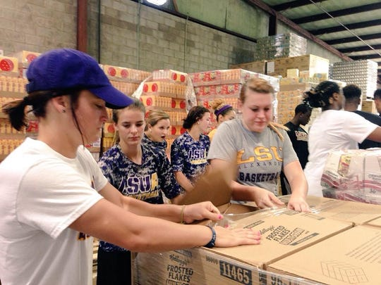 About 50 Louisiana State University of Alexandria freshmen students, Ambassadors and athletes unload food and pack backpacks at the Food Bank of Central Louisiana on Friday. The volunteer community service is part of freshman orientation.