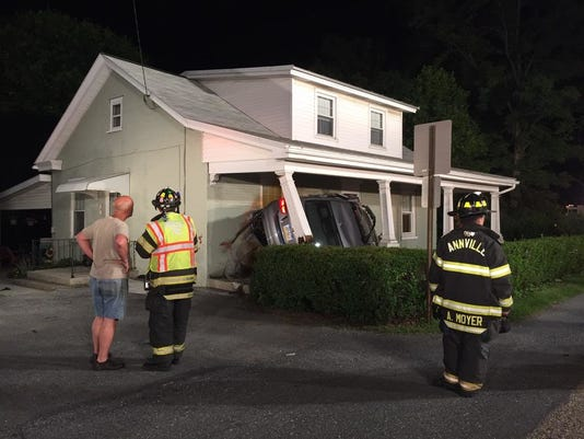 Firefighters work to remove the vehicle that crashed into the front porch of a house on Sunday, June 7, 2015 in Annville, Pa.