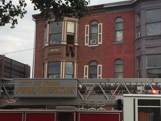 Firefighters respond to a call in the 600 block of West Market Street on Saturday. The pants hanging out the window were part of a Halloween costume and were placed there before the fire, a resident said.