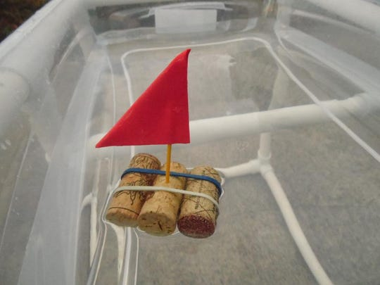A sailboat made out of wine corks floats in a homemade water play area.