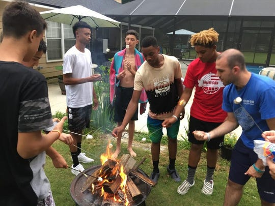 Youth basketball players from Italy and North Carolina roast marshmallows at the home of Al and Sandra Blizzard Sunday.