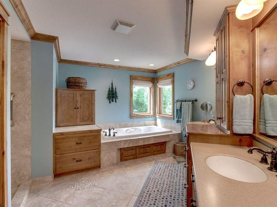 This master bathroom features a whirlpool, dual vanity and heated floor.