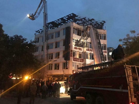 In this photo provided by Sivanand Chand, a hotel guest who was rescued, firefighters rescue people during an early morning fire at the Arpit Palace Hotel in the Karol Bagh neighborhood of New Delhi, India, Feb.12, 2019. More than a dozen people were killed.