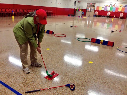 Paula Dechert, executive director of The First Tee of Central Louisiana, demonstrates a swing at a National School Program professional development session for Rapides physical education teachers at Alma Redwine Elementary New Vision Academy on Friday.
