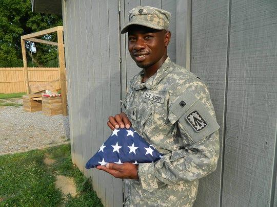 Spc. Corderra Dews with his re-enlistment flag.
