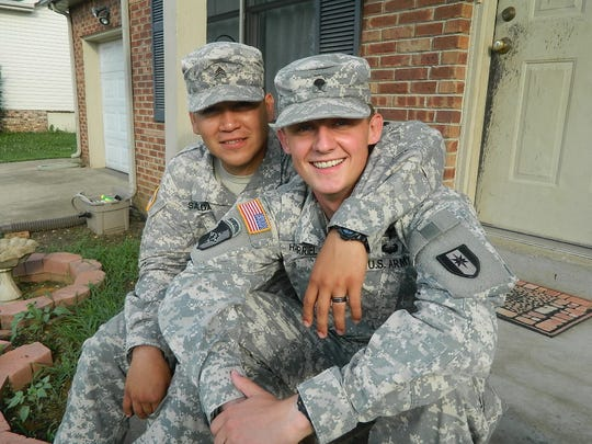 Married couple Sgt. Cristian Saldana and Spc. Nicholas Harriel in front of their home.