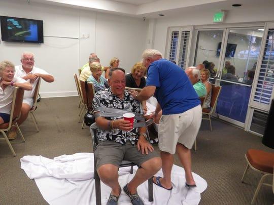 Vice Commodore John Queen gets a haircut.