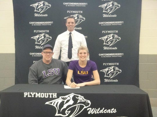 Olivia Beyer takes part in a signing ceremony Wednesday. She will play Division I volleyball at Louisiana State University. Seated next to her is her dad, Jonathan Beyer. Standing is Plymouth High School athletic director Kyle Meteyer.