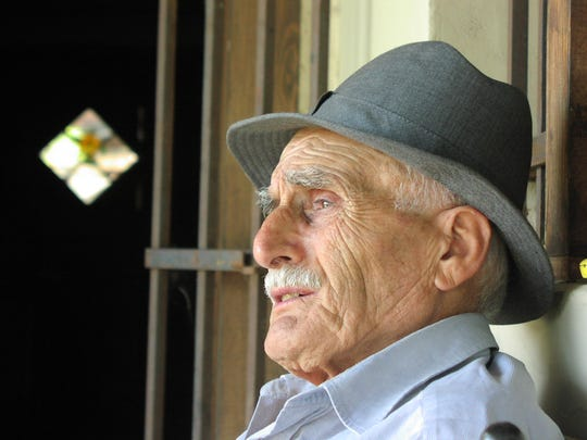 An elderly man sits on a porch. The elderly may benefit from a geriatrician for health issues.