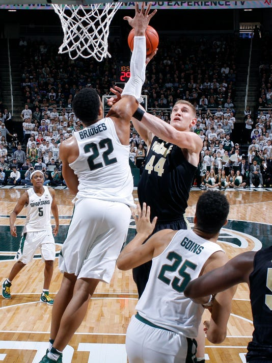 Purdue's Isaac Haas (44) shoots against Michigan State's Miles Bridges (22) and Kenny Goins (25) during the second half of an NCAA college basketball game, Tuesday, Jan. 24, 2017, in East Lansing, Mich. Purdue won 84-73. (AP Photo/Al Goldis)