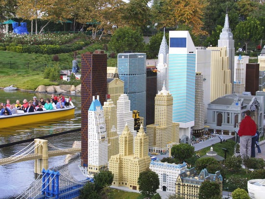 Visitors on foot and by boat view a miniature New York