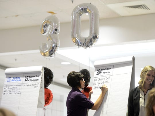 Volunteer Noelle Jarrett of Century National Bank writes down a bid for a cake below balloon celebrating the Carr Center's 30th anniversary this year during the Center's annual Cake Auction on Friday.