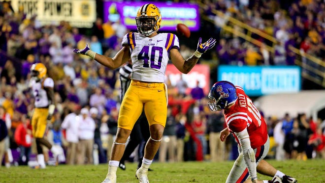 Oct 22, 2016; Baton Rouge, LA, USA; LSU Tigers linebacker Duke Riley (40) celebrates as Mississippi Rebels quarterback Chad Kelly (10) looks on following a defensive stop during the second half of a game at Tiger Stadium. LSU defeated Mississippi 38-21. Mandatory Credit: Derick E. Hingle-USA TODAY Sports