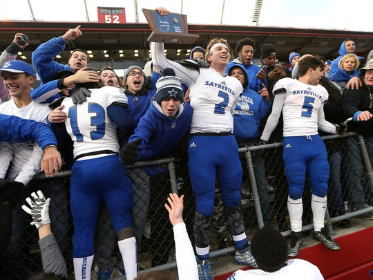 Sayreville quarterback Jayson DeMild celebrates in the crowd with the championship trophy after their come from behind win vs. Middletown North in North 2 Group IV sectional football championship at Rutgers University's High Point Solutions Stadium. Sayreville came from behind to win 41-14. Dec. 3, 2016, Piscataway, NJ.