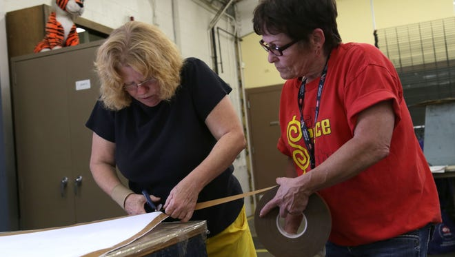 Karen Swinning and Laura Zimmer, of Progress Industries, help make a banner in support of first responders for the Labor Day Parade.