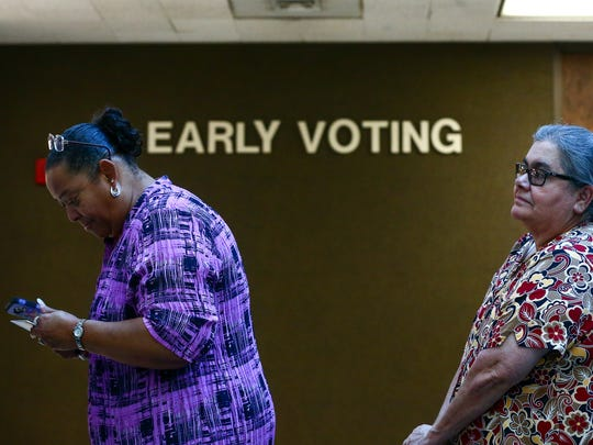 Voters stand in line at the Nueces County Courthouse to cast their ballot on the first day of early voting in the 2016 general election.