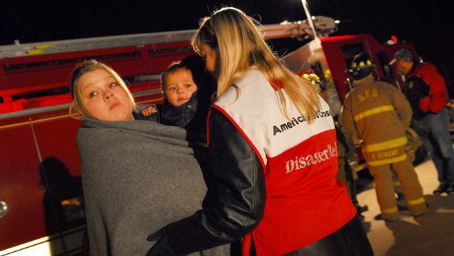 December 12, 2007. Red Cross worker Patsy McKenna talks with Haley Evans as she holds her son Braylon during the filming of an American Red Cross video reenactment of a house fire in Sandusky, Ohio.