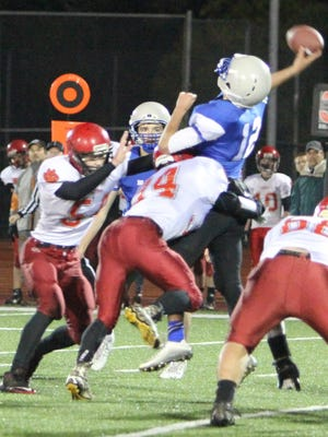 Blanchet quarterback R.J. Veliz gets off a pass under heavy pressure in a 32-12 win against Clatskanie in the first round of the OSAA Class 3A state playoffs on Saturday, Nov. 7, 2015.