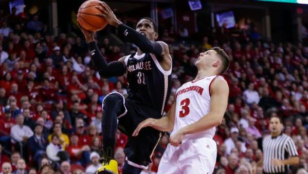 Milwaukee's J.R. Lyle (30) shoots against Wisconsin's Zak Showalter (3) during the first half of an NCAA college basketball game Wednesday, Dec. 9, 2015, in Madison, Wis. (AP Photo/Andy Manis)