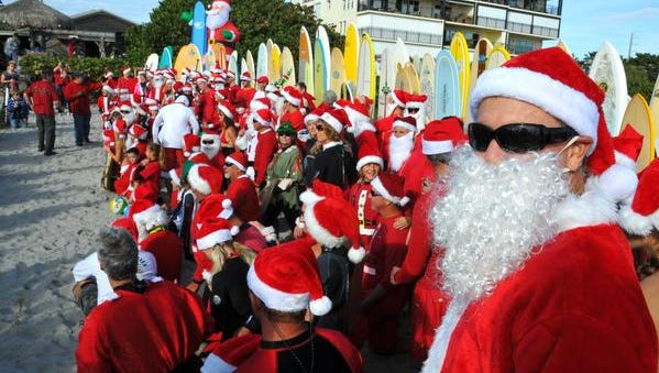 File photo of Surfing Santa event. The Surfing Santa event has been held at 24th St. South in Cocoa Beach for the last five years. George Trosset started  the whole thing behind his house in 2009 as a fun thing to do on Christmas Eve. It outgrew the location with hundreds of surfing Santa's and spectators showing up for the beachside Christmas Eve fundraiser. This year the city of Cocoa Beach is stepping up and the surfing Santa's are moving to Minutemen Causeway.
