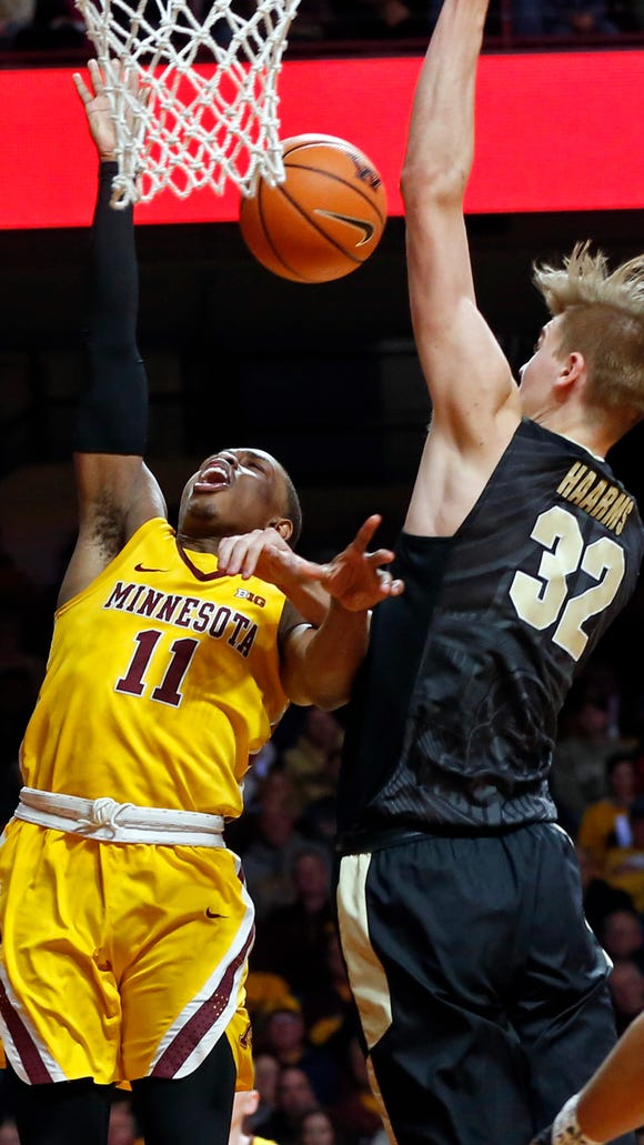 Minnesota's Isaiah Washington, left, is fouled by Purdue's