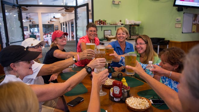 Women with the Treasure Coast chapter of the Executive Women's Golf Association toast their first drink at the Miles Grant Country Club in Port Salerno on July 19, 2017, after being kept from golfing because of lightning and rain. Making the best of their time together are, clockwise from top (orange shirt), Brigite Babine, of Palm City; Debbie Davis, of Palm City; Executive Women's Golf Association Golf Programs Manager Jenna Boyce, of Port Salerno; EWGA Treasure Coast Chapter President Sue Whittington, of Palm City; Sandy Lester, of Port St. Lucie; Terri Kudlinski, of Palm City; Carole Tannenbaum, of Palm City; Christine de Saint Genois, of Port St. Lucie; and Deb Miron, of Stuart.