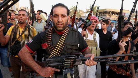 Iraqi Shiite tribal fighters deploy with their weapons while chanting slogans against the al-Qaida-inspired Islamic State of Iraq and the Levant to help the military defend Baghdad.