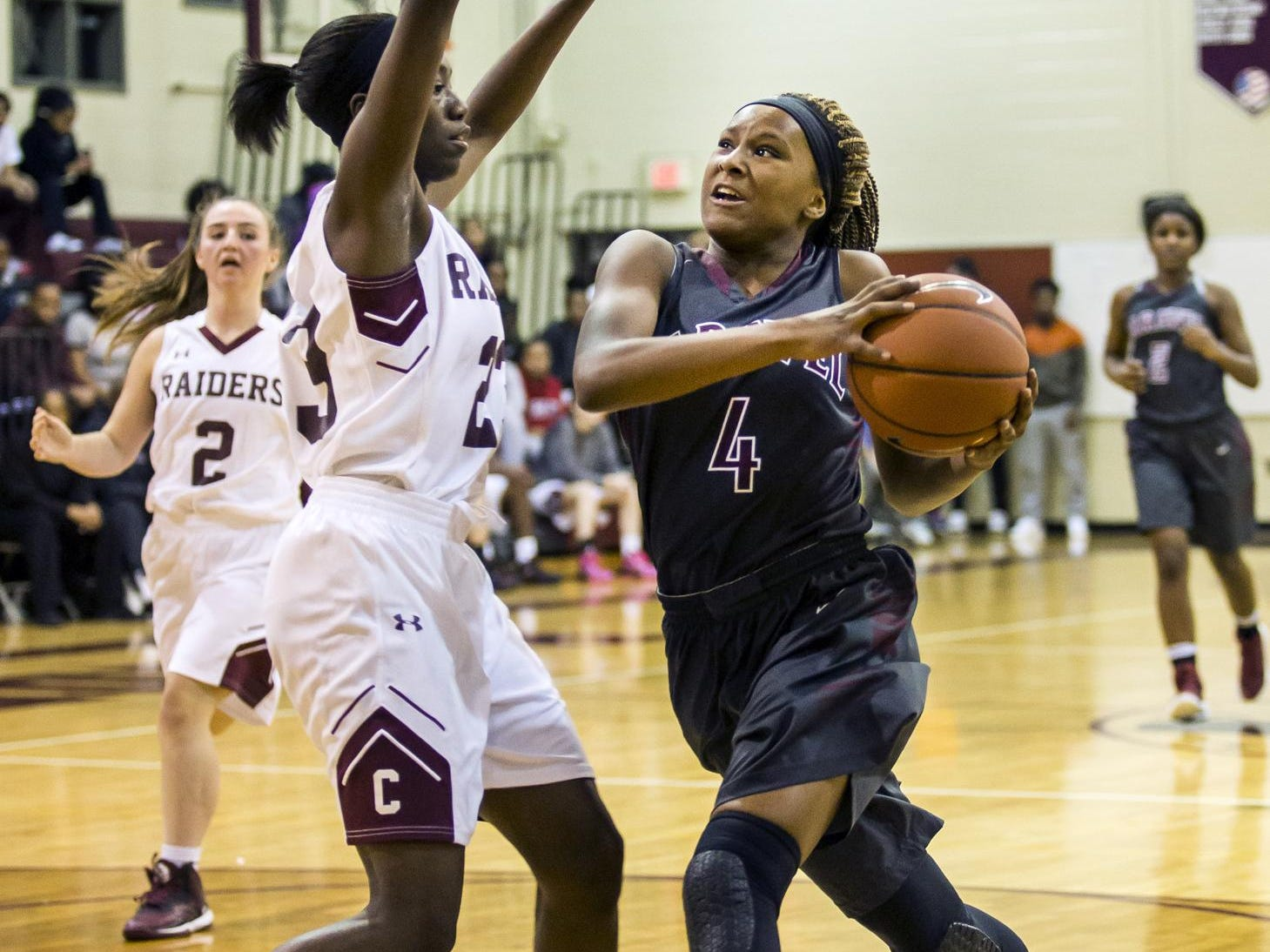 Caravel's Sasha Marvel (No. 4) drives to the basket as Concord's Zhan'e Snow defends in the second half of Caravel's 42-26 win over Concord at Concord High School on Monday night.