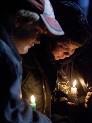 Weston High School sixth graders Clayton Jennings, 11, left, and Riley Anderson, 12, cry during a candlelight vigil on the football field Friday, Sept. 29, 2006, in Cazenovia, Wis.