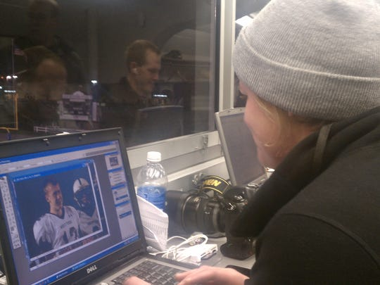 That's photog Kate Penn hard at work editing her photos after the game.