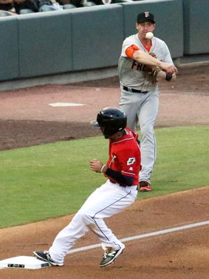 Carlos Asuaje, bottom, of the El Paso Chihuahuas, reaches third base as Fresno third baseman Matt Duffy throws to first after scooping up a ground ball Friday night at Southwest University Park.