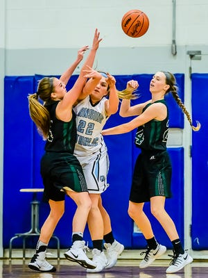 Meghan Gillespie ,22, of Lansing Catholic passes out of a double team by Maddie Watters ,left, and Kenzie Lewis of Williamston.