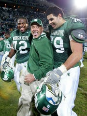 Michigan State coach John L. Smith, center, celebrates with Stefon Wheeler (72) and Sean Poole (79) following a 49-14 win over Wisconsin Saturday, Nov. 13, 2004, in East Lansing, Mich. (AP Photo/Al Goldis)